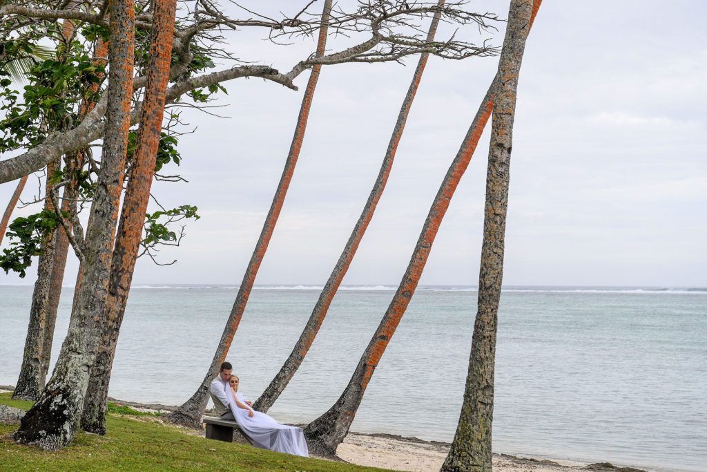 The newly weds cuddle against the towering palms of Shangri La Fiji