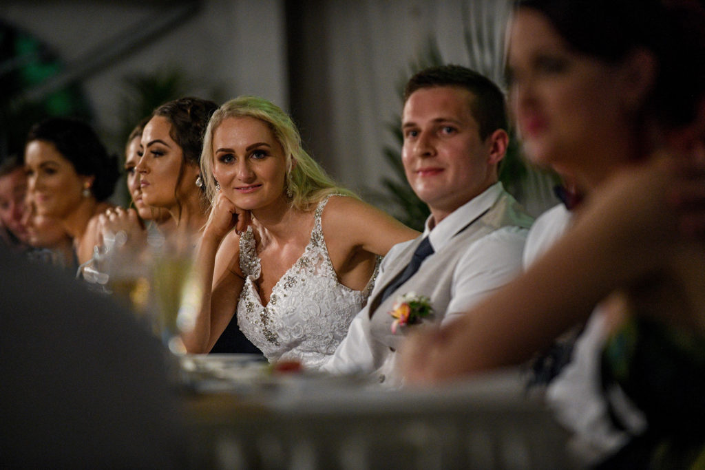 The newly weds lean forward as they listen to the bride's dad's speech