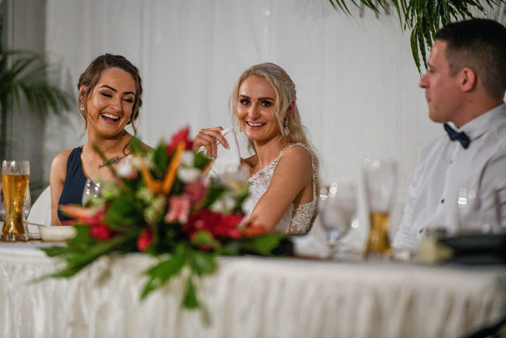 The bride laughs as she listens to a wedding speech