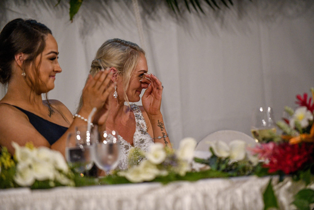 The bride wipes a tear as she listens to the wedding speeches