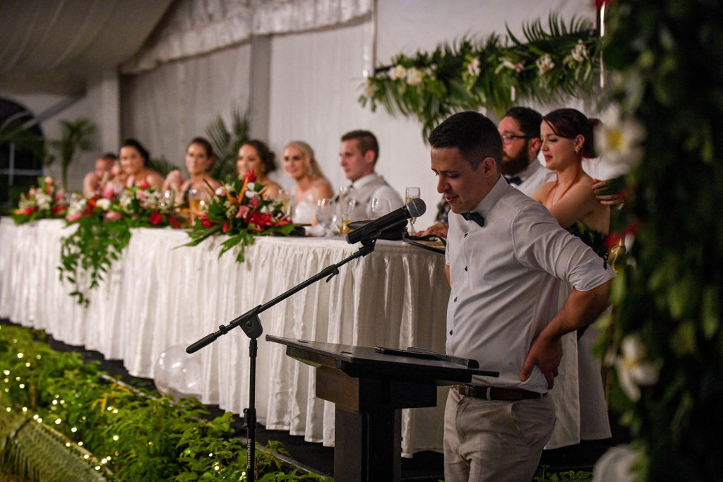The groom's brother reads a speech at the wedding reception