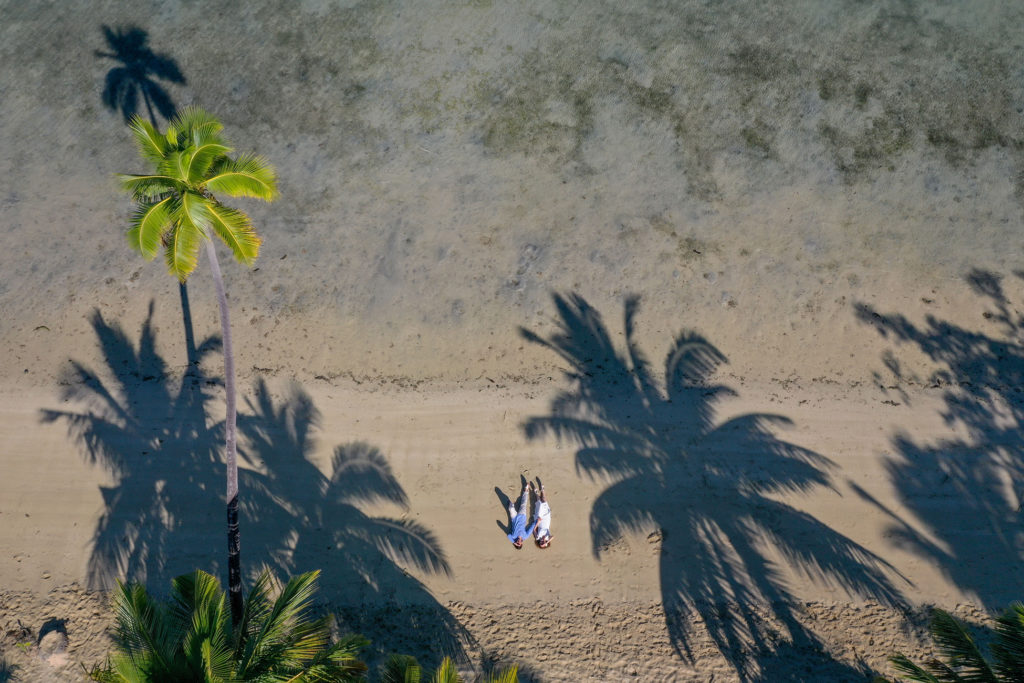 A stunning drone shot of the loving couple under the towering shadows of Malolo Island palm trees