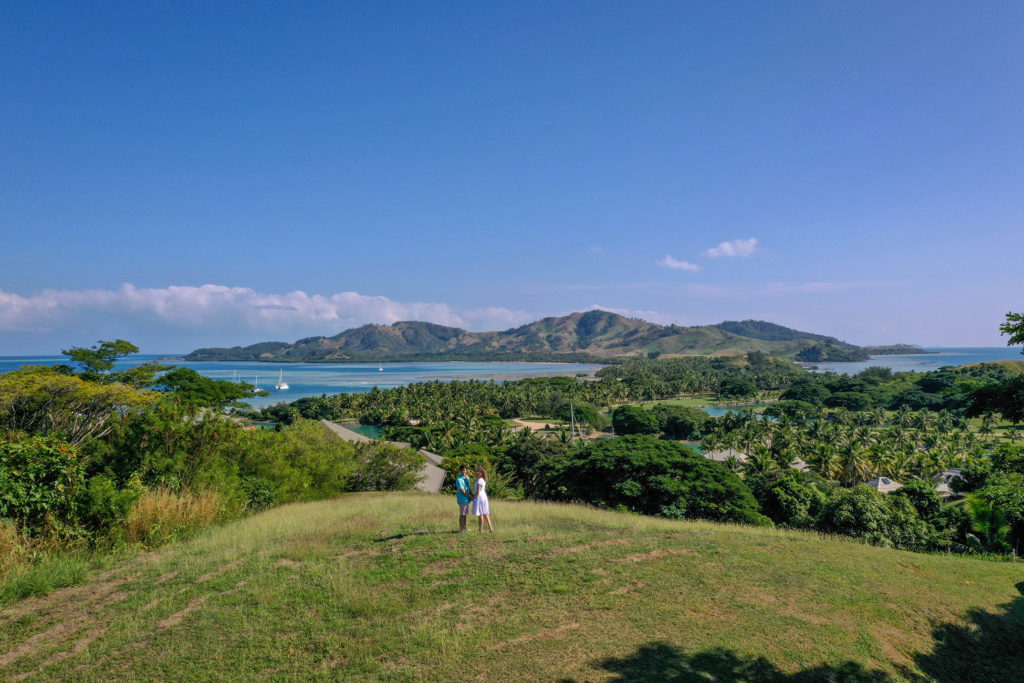 A drone shot of the couple staring at the landscape view of Malolo Island Fiji