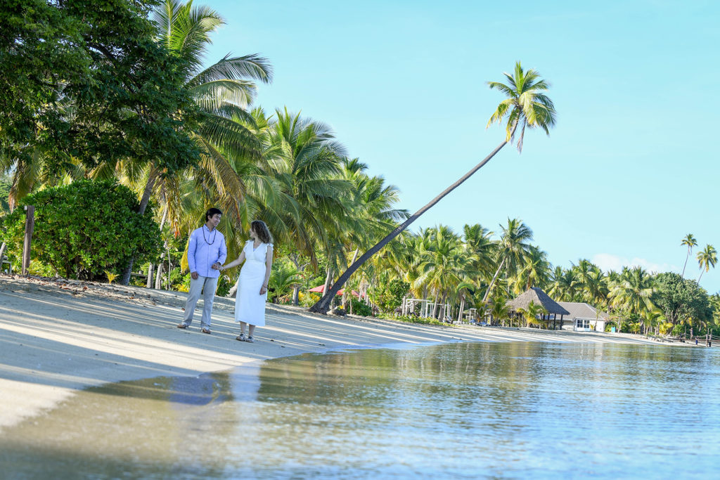 The loving couple strolls along the Pacific ocean against towering Fiji palms