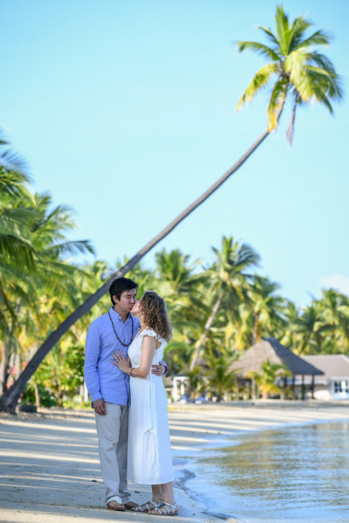 The loving couple shares a passionate kiss on the beach against towering Fiji palms
