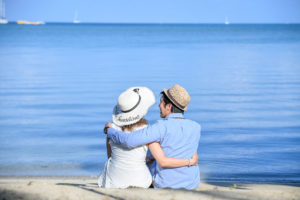 The couple cuddles while staring into the deep blue Pacific ocean