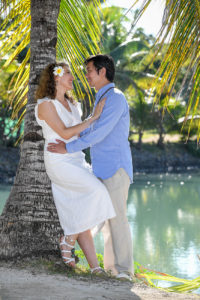 The loving couple embrace against a palm tree