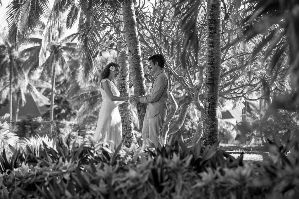 A monochrome frame of the loving couple holding hands under the palm trees of Malolo Island Fiji