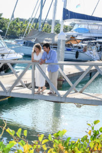 The couple stand on a dock as they admire the sea