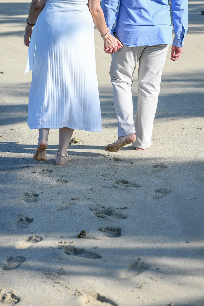 The honeymooning couple leaves footprints in the sand