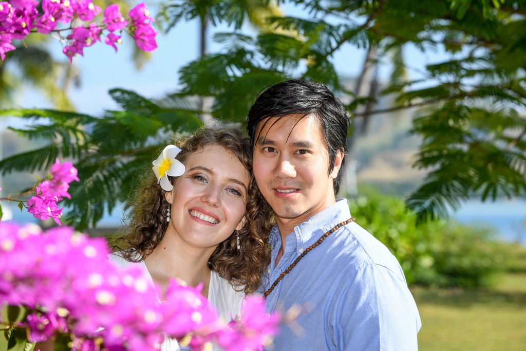 The loving couple is framed by purple Fiji flowers