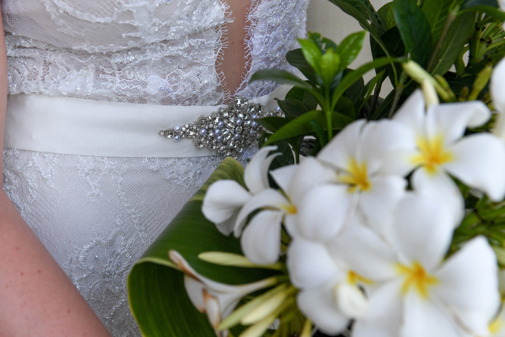 Detail of the bride's diamond waist brooch against white frangipani flowers