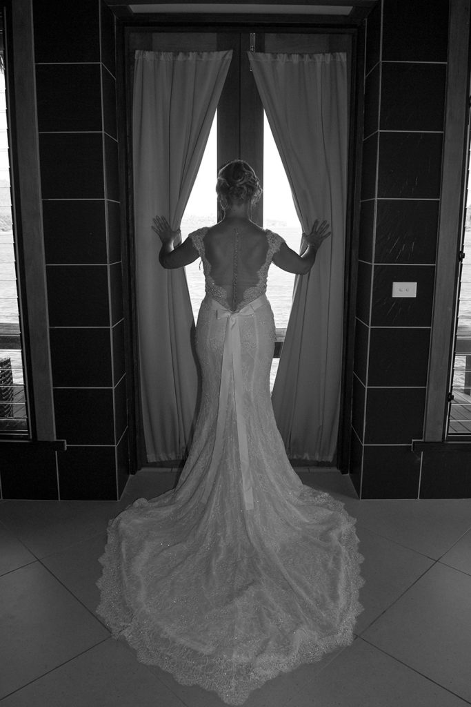 A monochrome image of the bride posing in the window with her bareback wedding gown