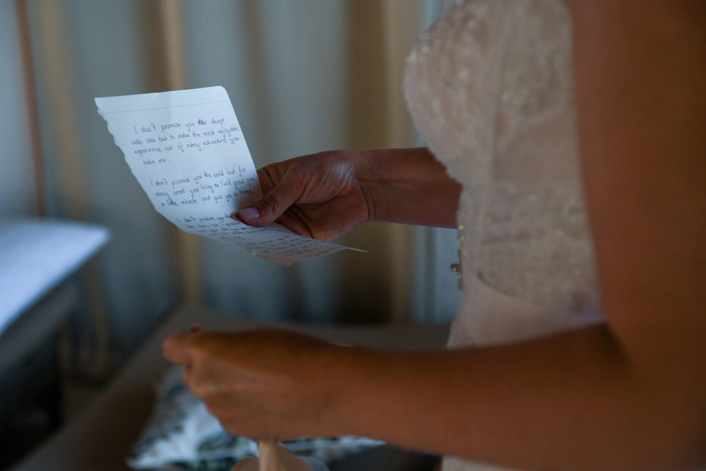 The bride reads a note from the groom before the wedding