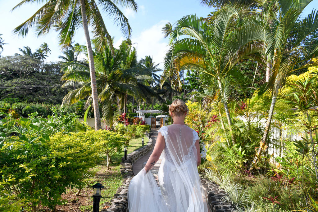 The bride walks down an aisle of towering Fiji palm trees
