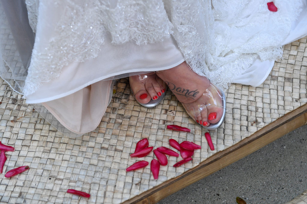 Rose petals at the foot of the bride's clear strapped heel