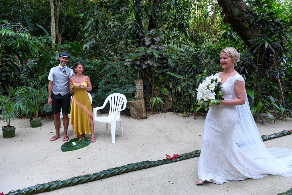 The bride walks down the sand aisle as wedding guests watch