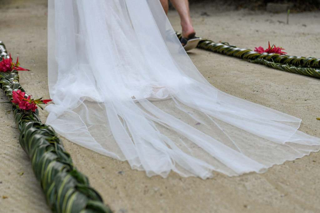 The bride's wedding train being dragged along the sand