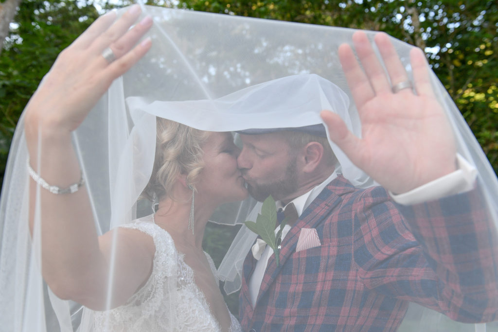 The loving couple passionately kiss under the bride's veil