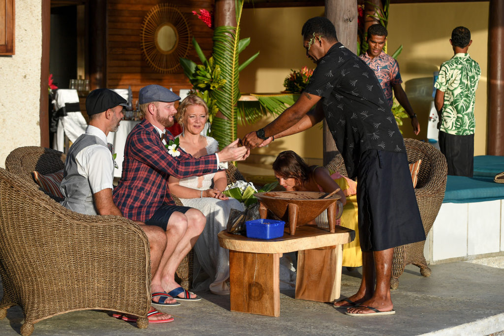 The waiter gives the groom a drink from the kava ceremony