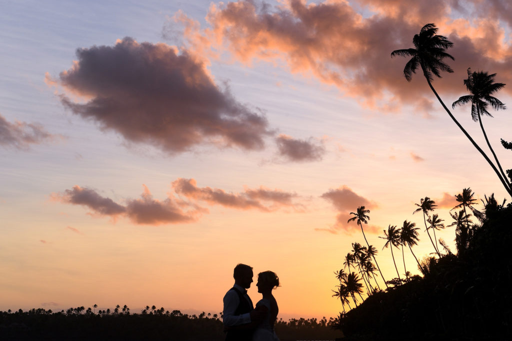A silhouette of the newly weds under Fiji palms and a sunset