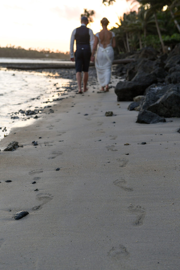 The newly weds leave footprints in the sand at Koro Sun beach