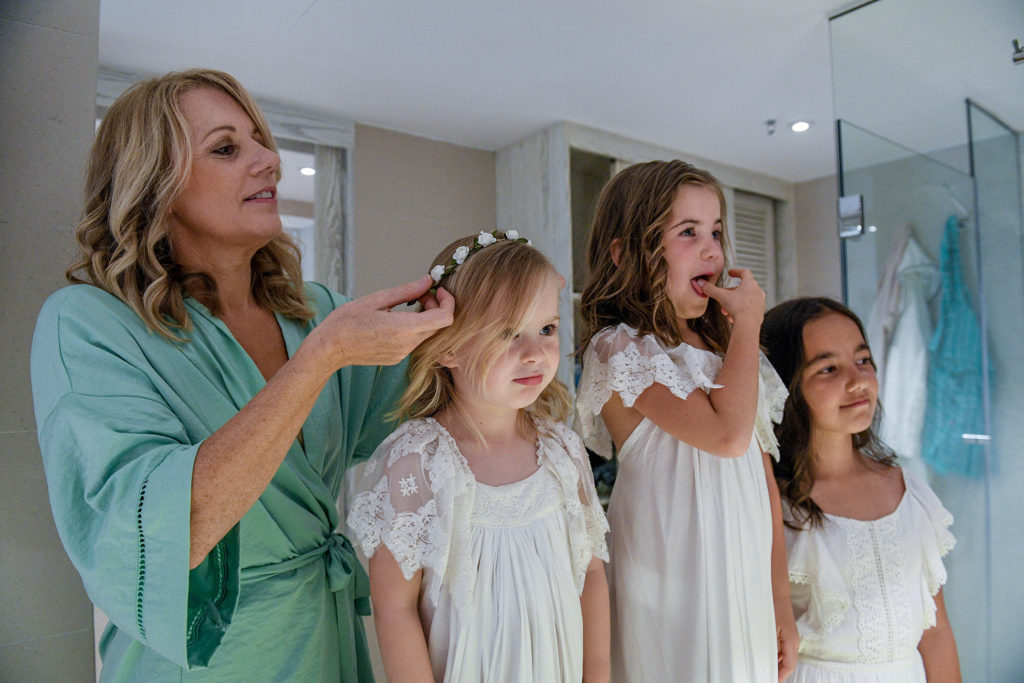 The flower girls admire their gorgeous hairdos in the mirror.