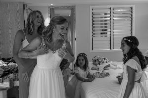A monochrome image of the the happy bride fitting her wedding dress