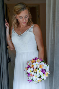 The stunning bride poses in the doorway holding her multicoloured bouquet