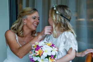 The bride pinches the cheeks of her cute flower girl daughter