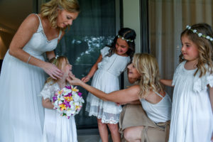 The bride and the flower girls share a light moment before the wedding ceremony