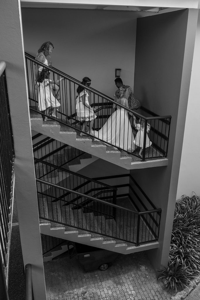 The bride and her flower girls make their way down a winding staircase