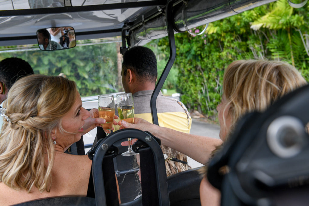 The bride and her bridesmaid toast a glass of champagne as they make their way to the wedding ceremony in a golf cart