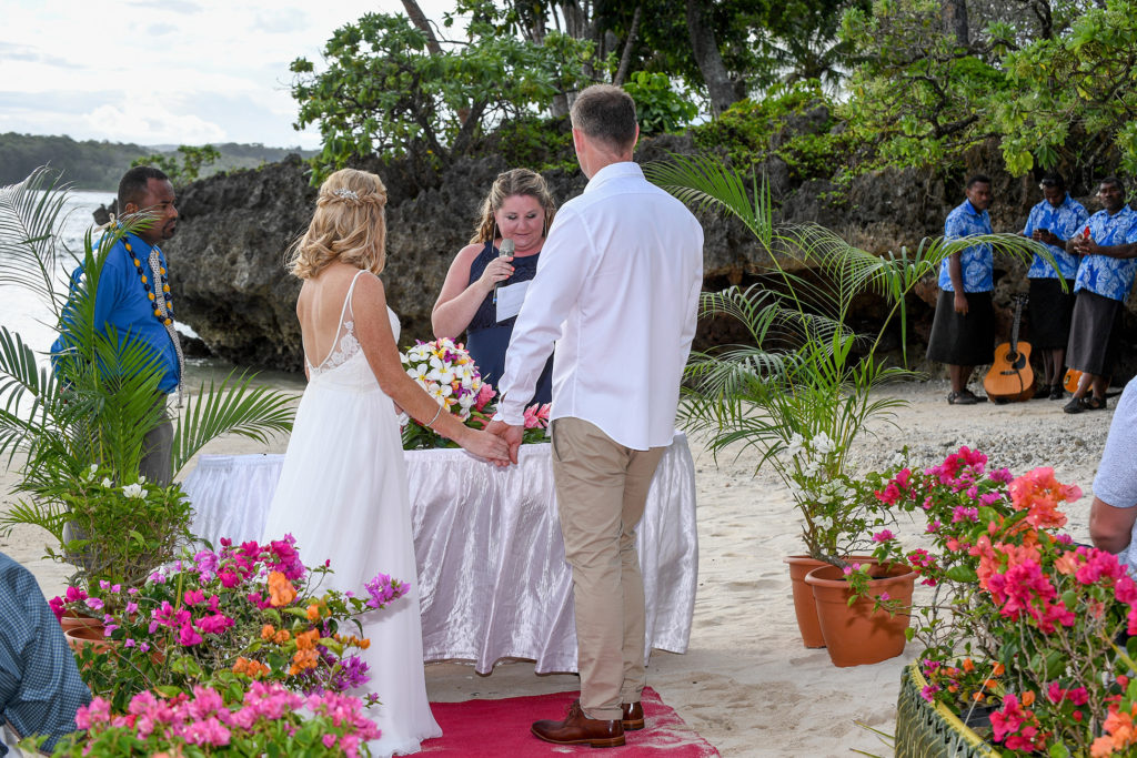 The bride and groom hold hands at the beachside altar overlooked by Shangri La