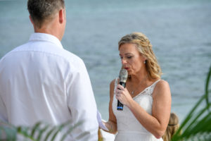 The bride reads her vows while standing at the altar overlooking the Pacific Ocean