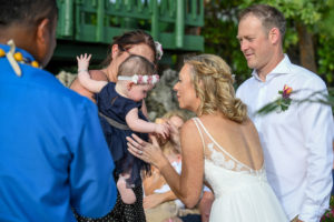 The bride hugs a cute little baby while at the wedding ceremony