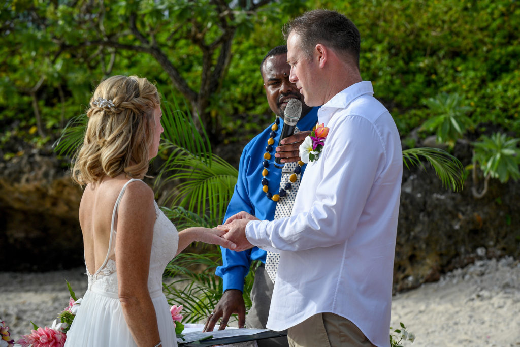 The groom says his vows as he slips the ring onto the bride's finger