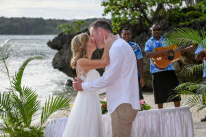 The newly weds kiss overlooking the glorious Pacific ocean
