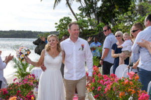 The newly weds happily walk down the aisle cheered by guests