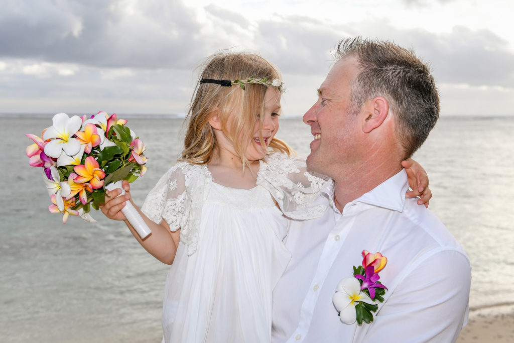 The flower girl sits on the groom's lap at Shangri La beach