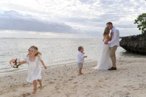 The flower girl and best boy photobomb the newly wed couple's kiss