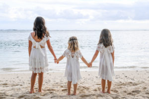 The three flower girls hold hands as they overlook the Pacific Ocean at Shangri La Beach