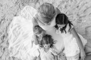 An overhead monochrome portrait of the bride hugging her three daughters