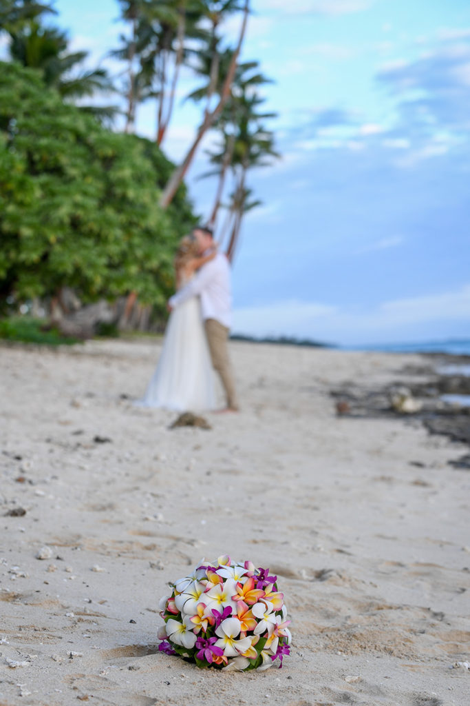 The camera focuses on the bouquet while the newly weds share a passionate kiss on Shangri La beach in the background