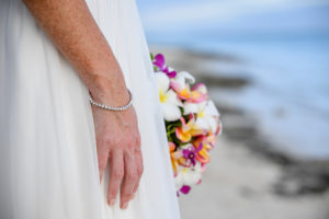 The bride's diamond bracelet and colourful frangipani and tropical flower bouquet