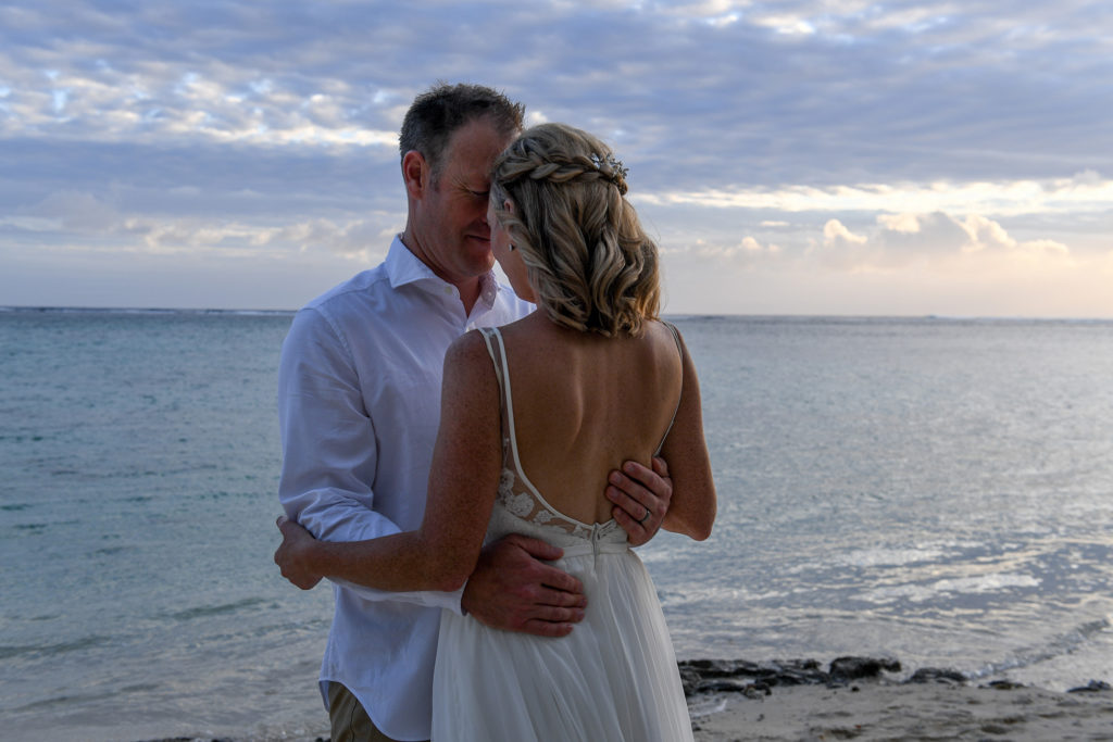 The newly wed couple embrace against the grey sunset of Shangri La Beach in Fiji