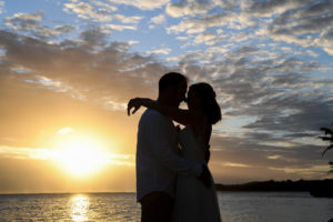 A silhouette of the newly weds kissing at sunset at Shangri La Fiji